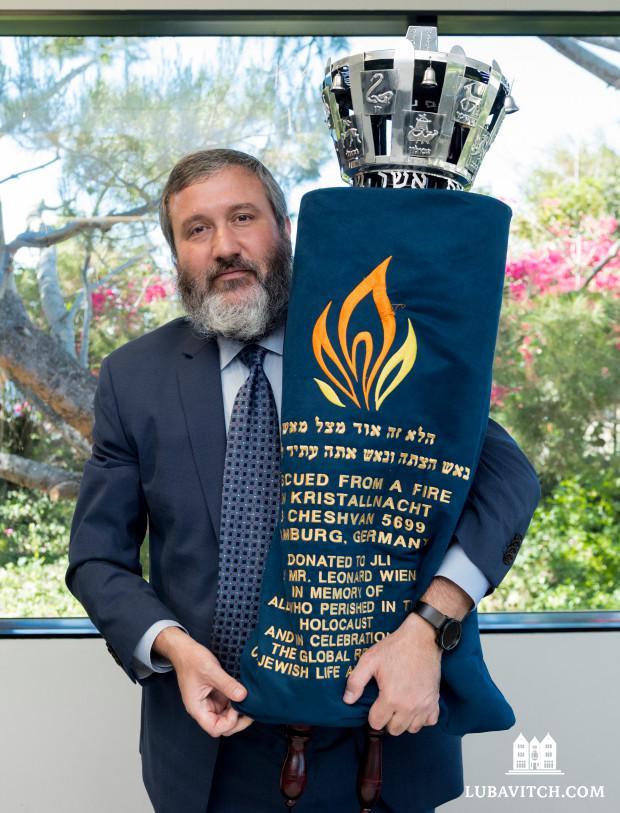 Rabbi Reuven Mintz holds a Torah rescued during Kristallnacht in Hamburg, Germany